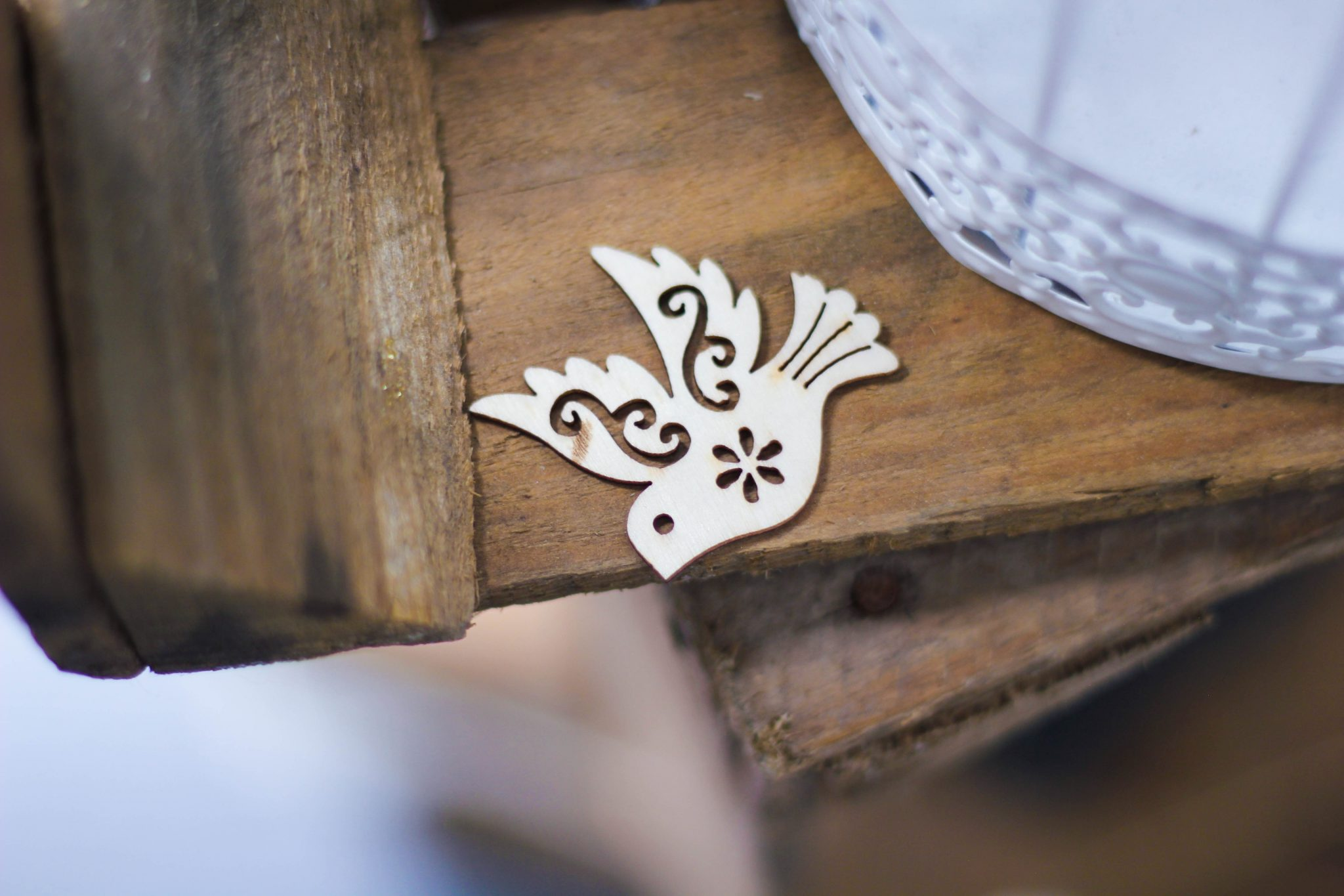 Wooden cutout of a dove on a table.