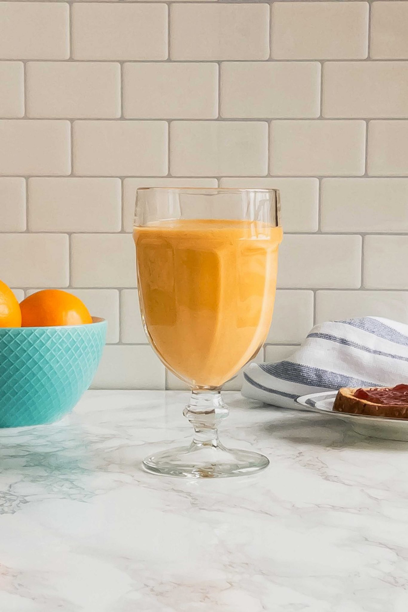 Sunshine Smoothie on a table with toast and a bowl of oranges.