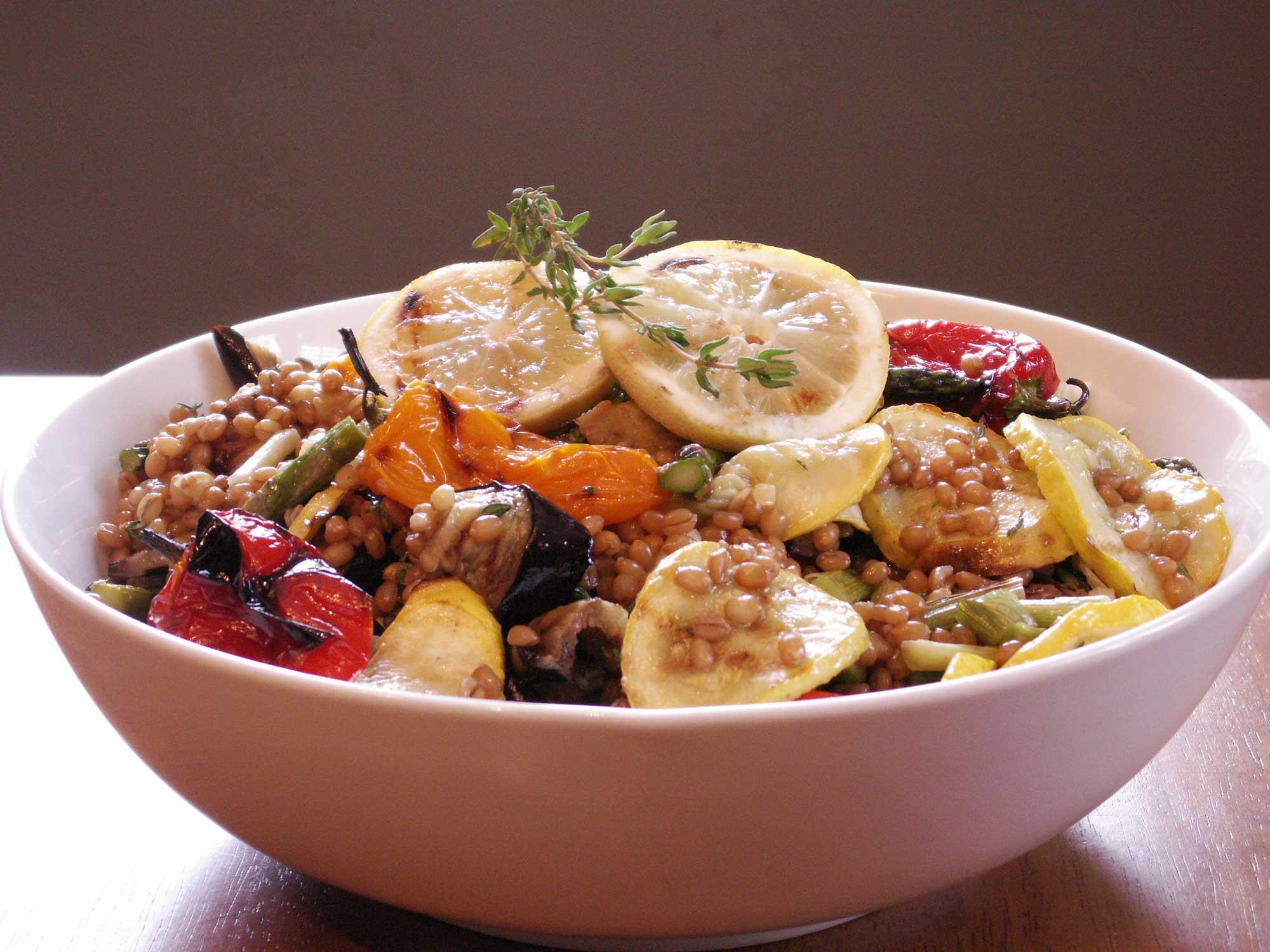 Grilled vegetable and wheat berry salad in white bowl.