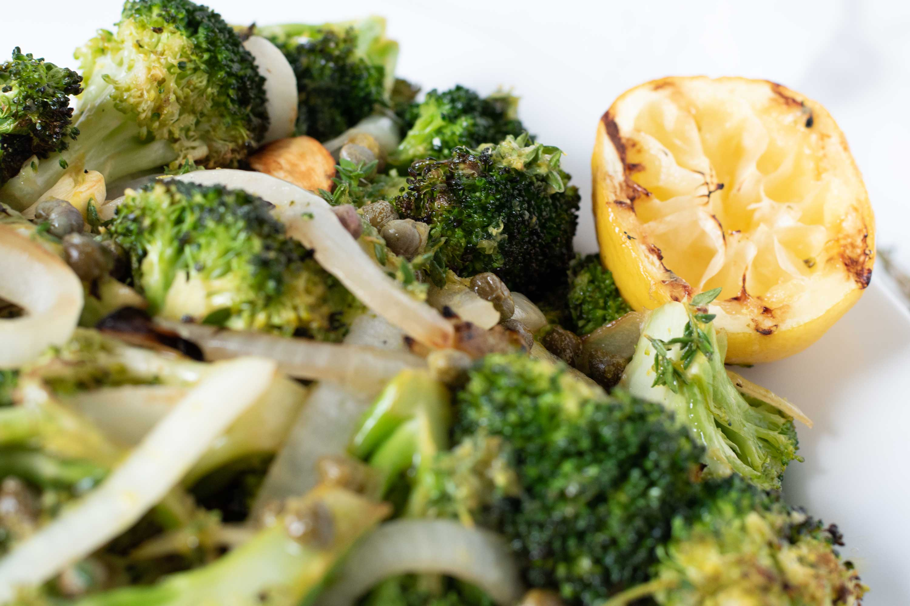 Close up of grilled broccoli and onions.