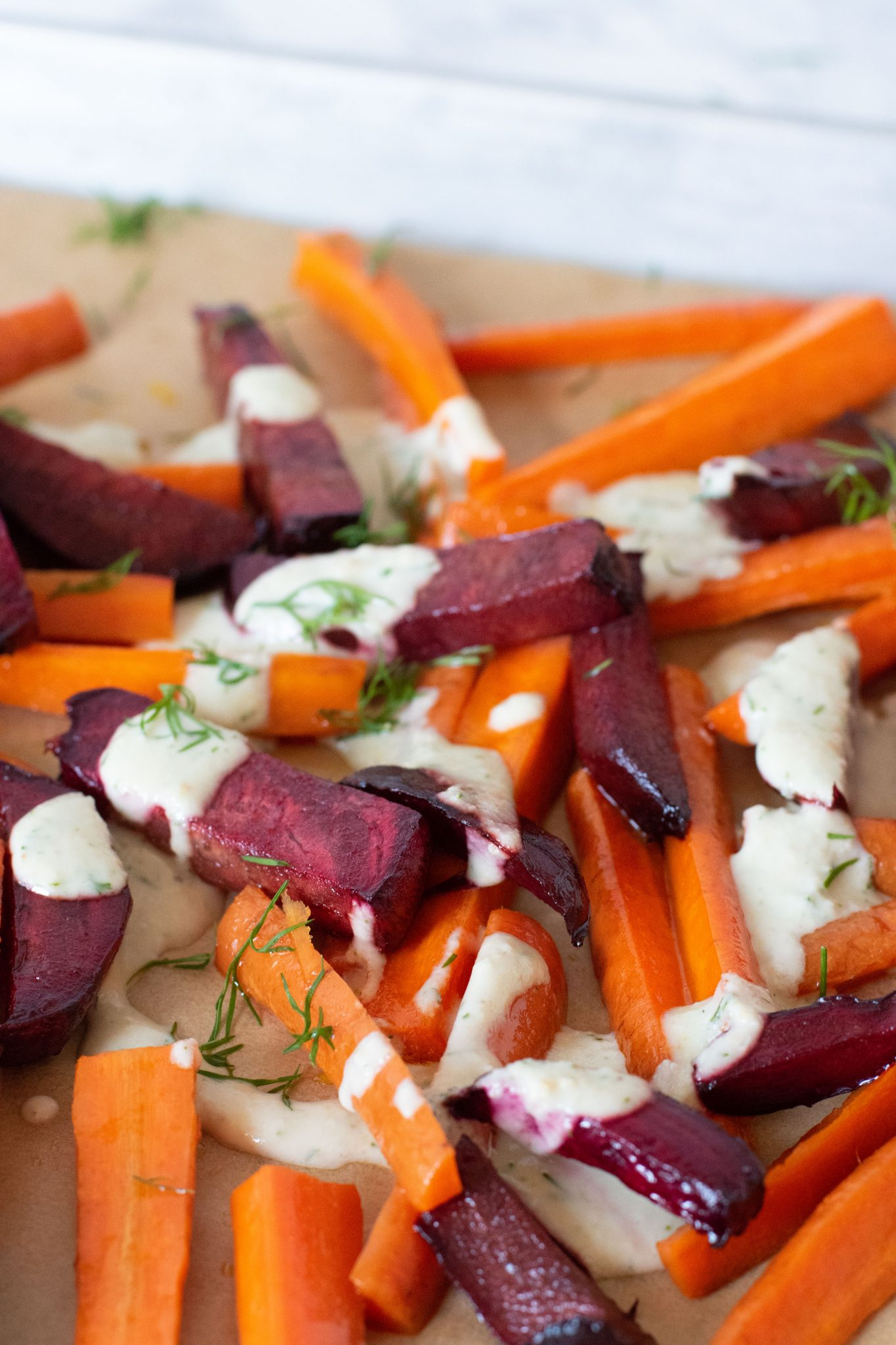 Roasted Beets and Carrots on a baking sheet, drizzled with garlic dill sauce