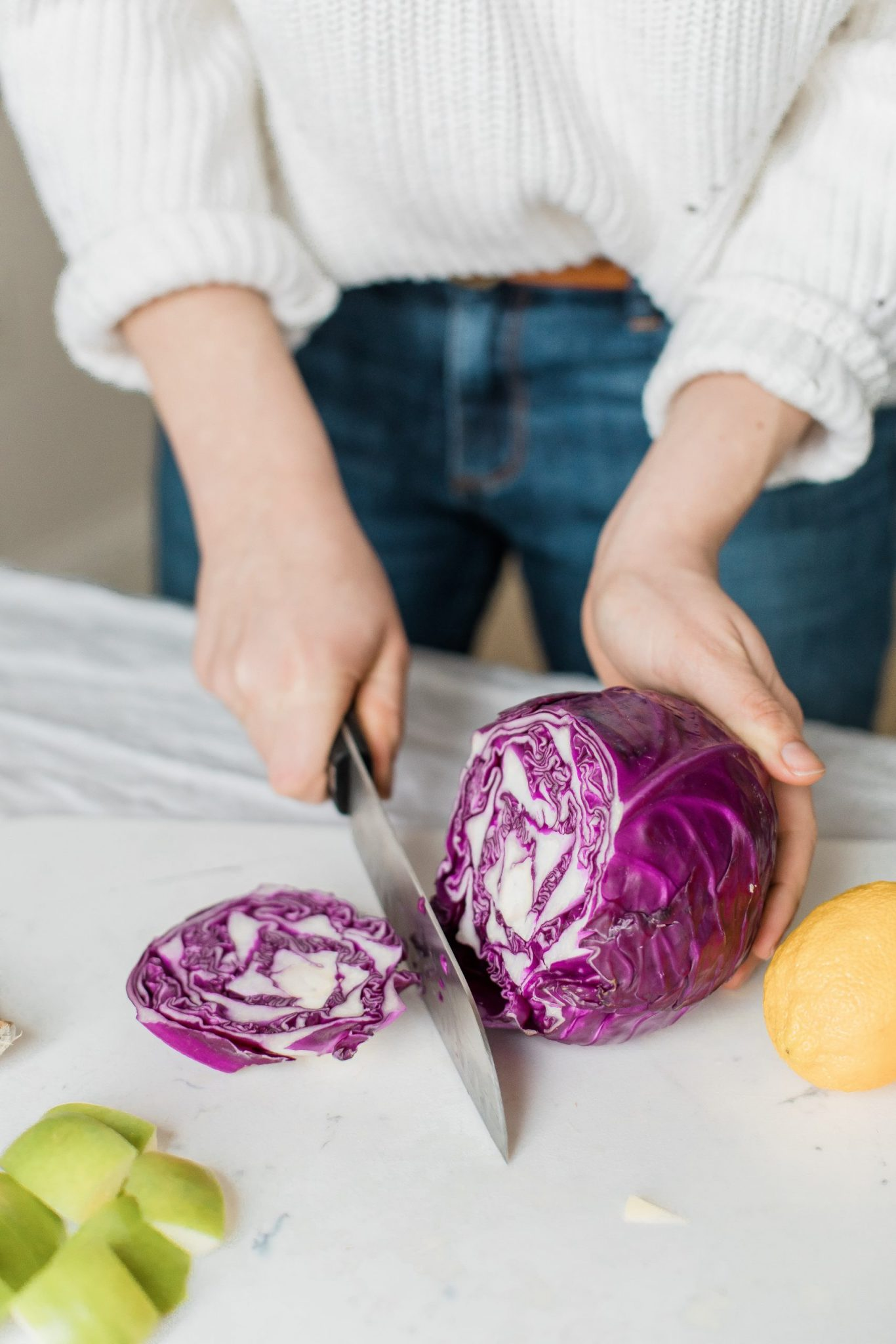 woman chopping purple cabbage with chef knife to develop heart healthy eating habits.
