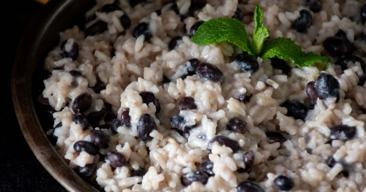 Close up of banana coconut rice and black beans on a round metal plate, garnished with mint, on a dark background.