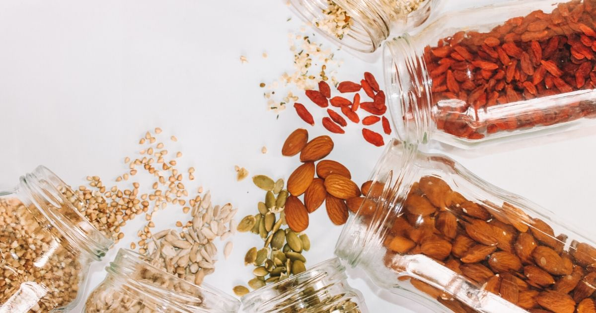 Jars of dried fruit, nuts and grains, on their sides, in a semi circle spilling out contents