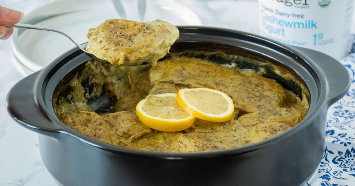 Pesto scalloped potatoes in black casserole dish, with a spoonful being lifted out