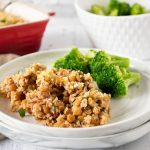 A scoop of Italian Lentil & Rice casserole on a plate with steamed broccoli.