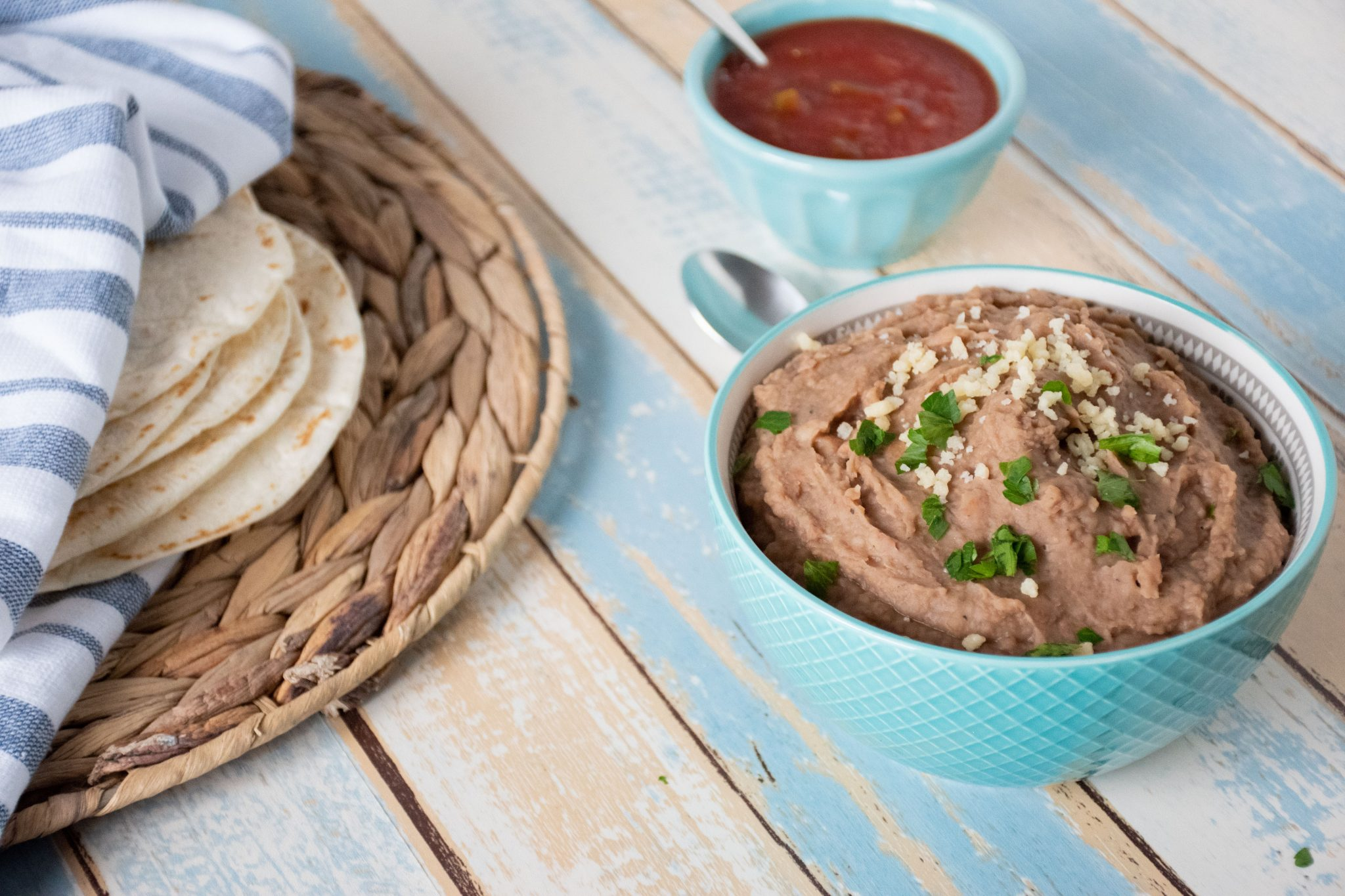 Blue bowl filled with refried beans, with tortillas and salsa in the background