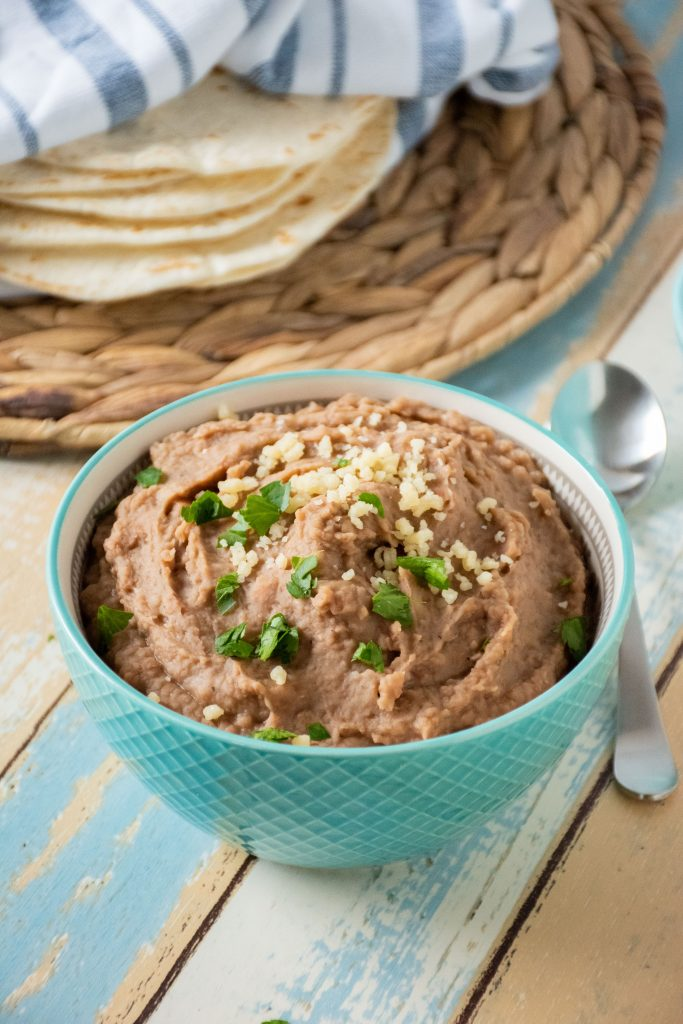Blue bowl filled with refried beans.