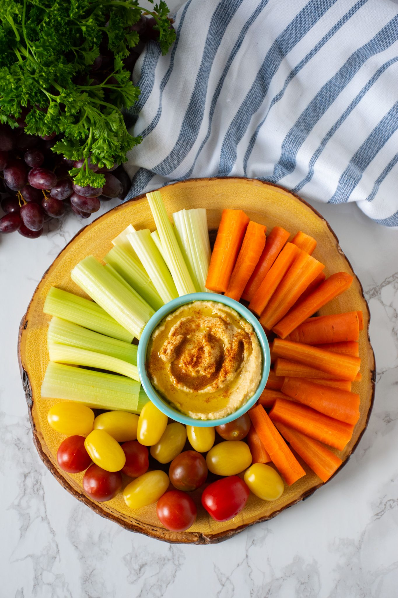 Overhead shot of vegetable platter with a bowl of pantry basics hummus.