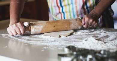 Woman rolling out dough with a rolling pin.