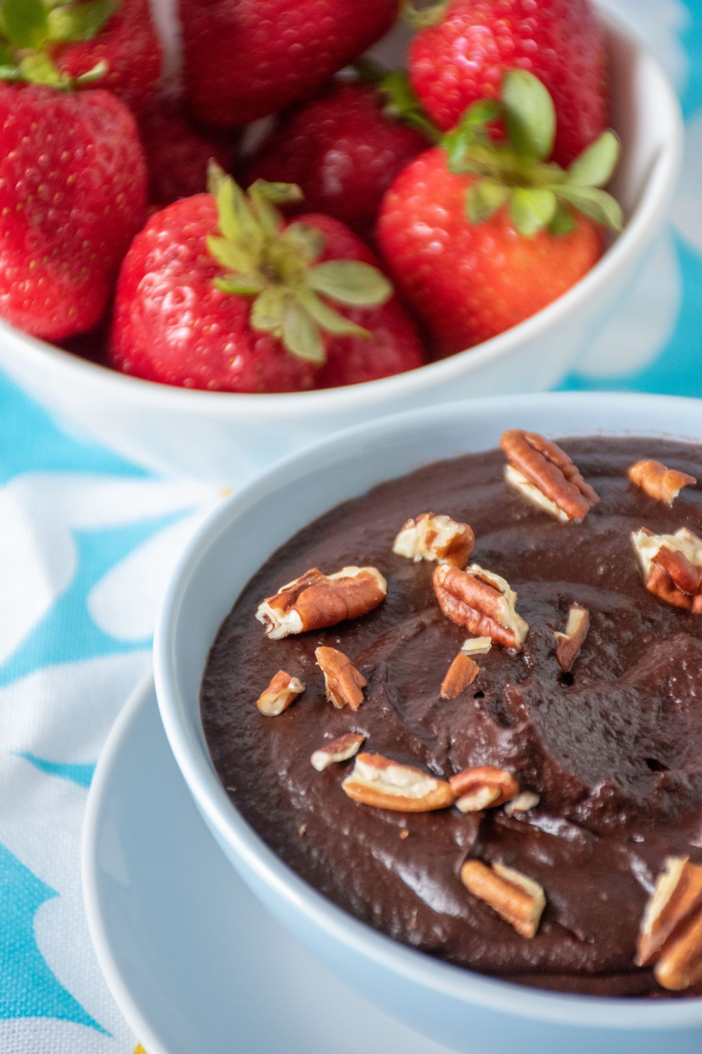 Close up of brownie batter in a bowl with pecan pieces on top. A bowl of strawberries is seen behind.