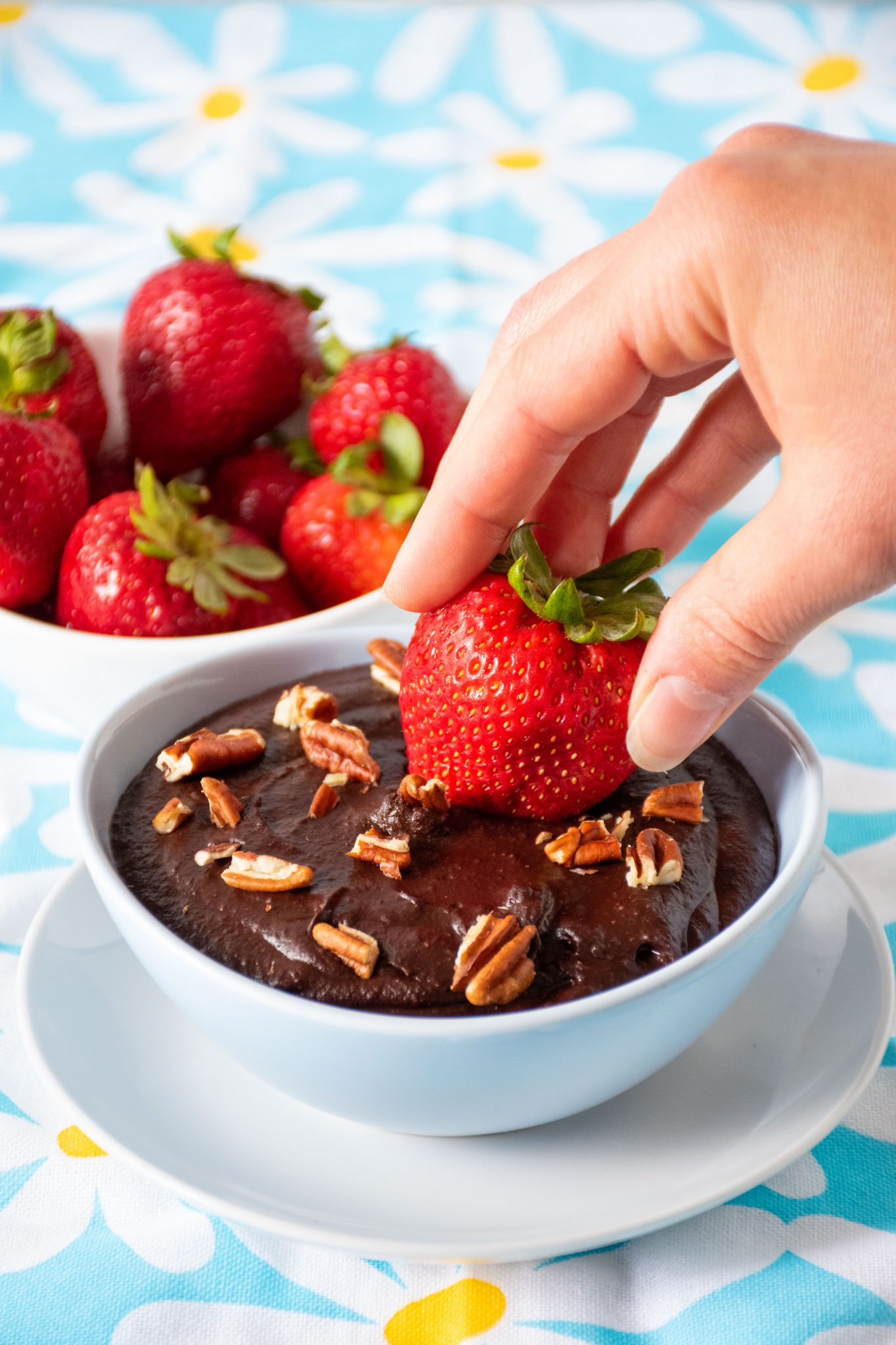 a strawberry being dipped into a bowl of brownie batter dip.