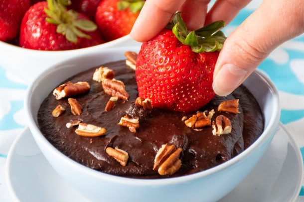Close up of a strawberry being dipped into brownie batter dip.