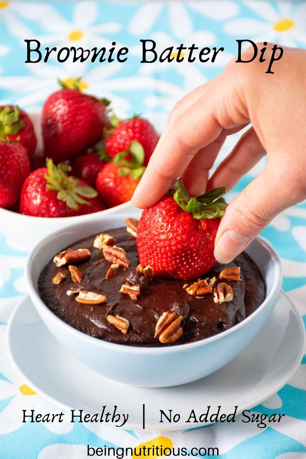 Brownie batter dip in a bowl with pecan pieces on top, and a hand dipping a strawberry in.