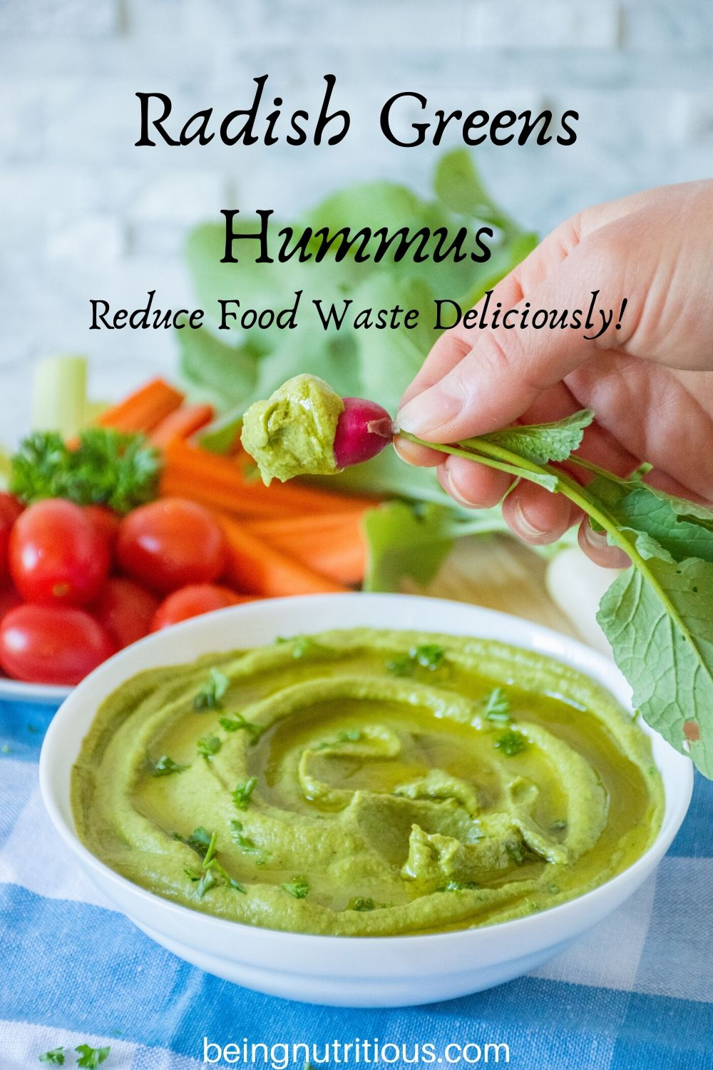 Radish Greens Hummus in a bowl with a hand dipping a radish in it.
