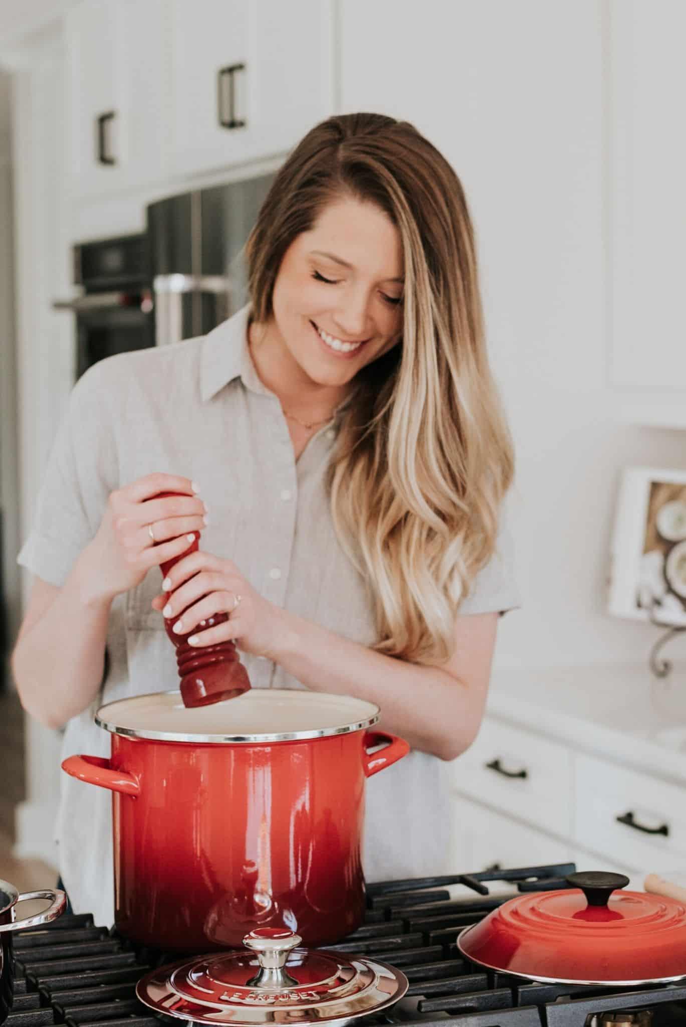 Woman adding salt to a pot on the stove