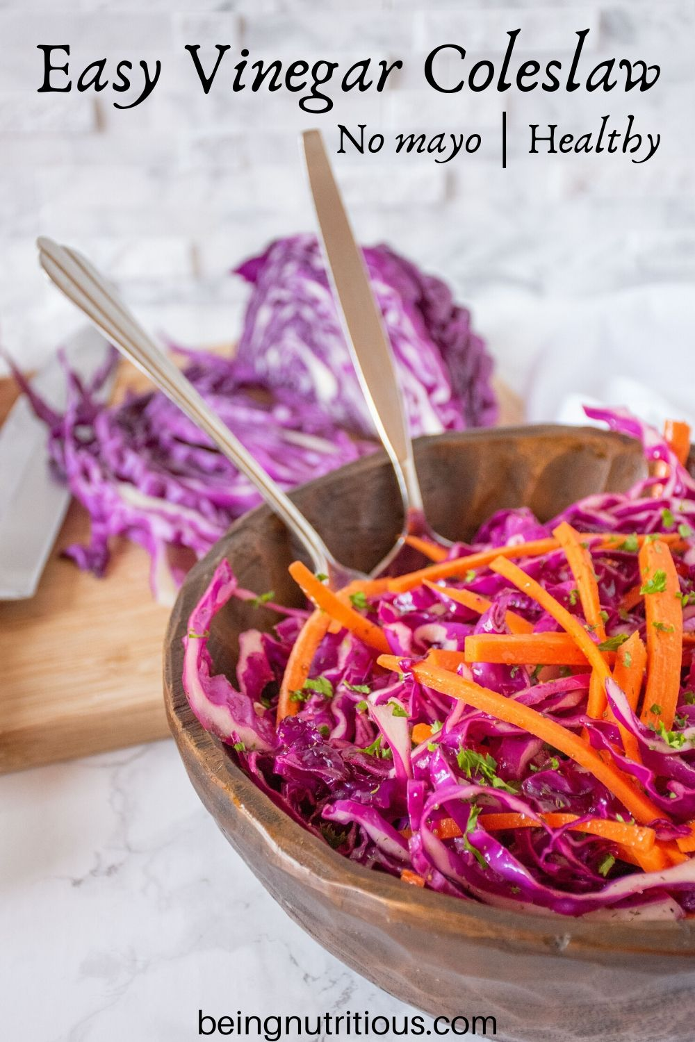 Easy vinegar coleslaw, in a wooden bowl, with shredded purple cabbage on a cutting board visible in the background.