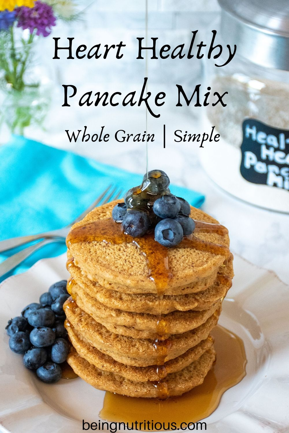 Stack of 6 whole wheat pancakes, with a pile of fresh blueberries on top, and syrup being poured over. Glass jar of heart healthy pancake mix is visible in the background.