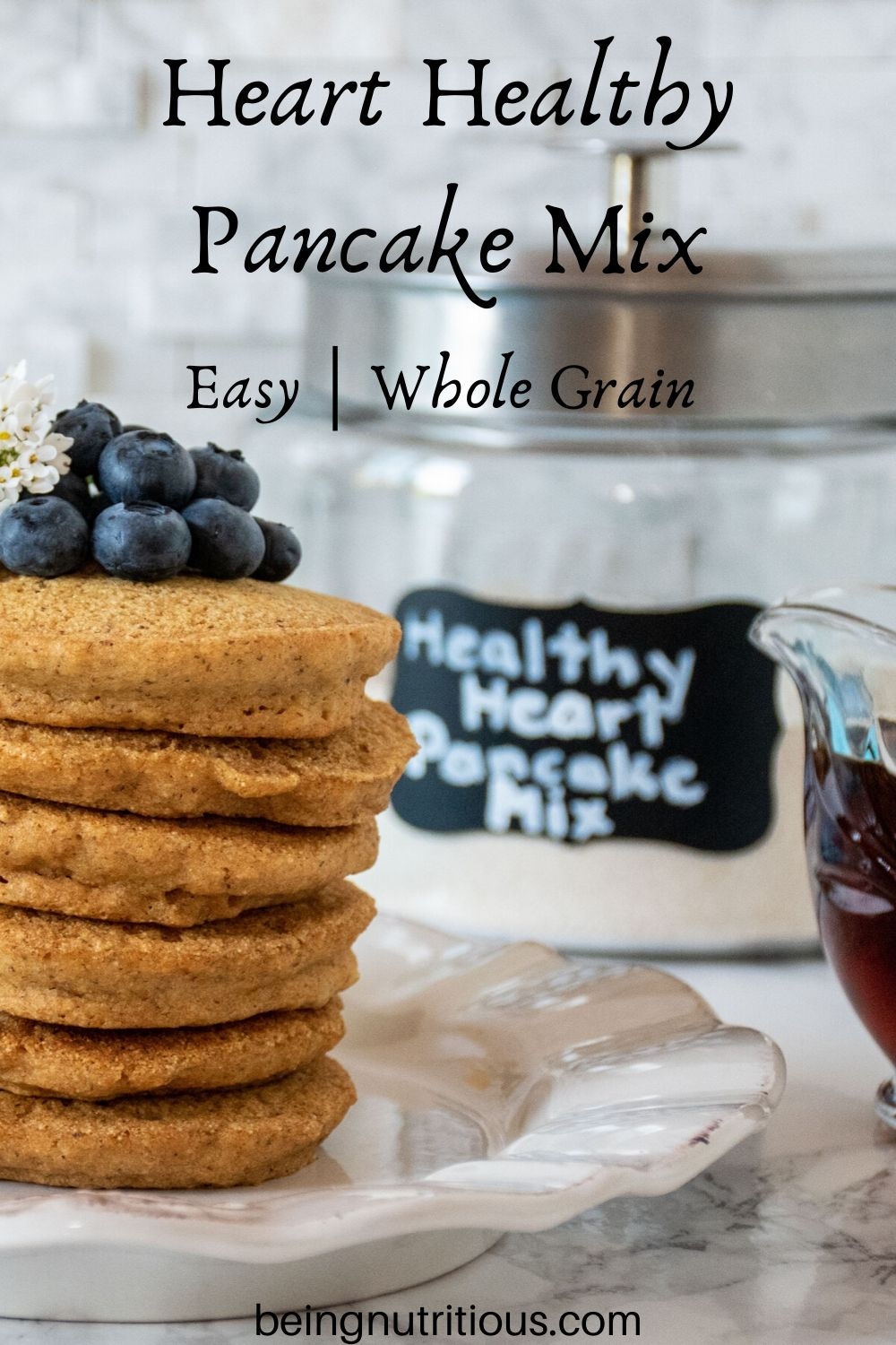 Stack of 6 whole wheat pancakes, with a pile of fresh blueberries on top. Glass jar that reads 'healthy heart pancake mix' is visible in the background.
