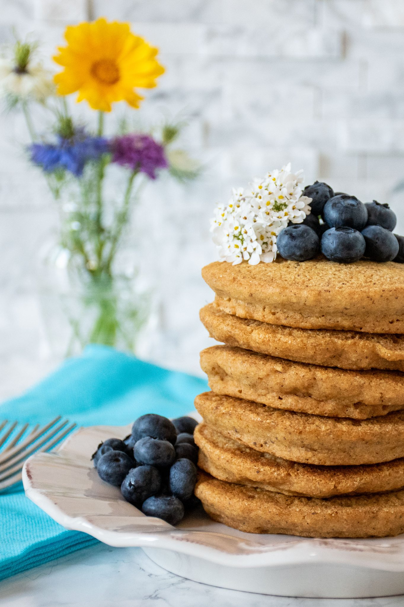 Stack of 6 whole wheat pancakes, with a pile of fresh blueberries and white flowers on top. A small bouquet of wildflowers is visible in the background.
