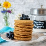 Stack of 6 whole wheat pancakes, with a pile of fresh blueberries on top, and piled to the right of the stack. Glass jar that reads 'healthy heart pancake mix' is visible in the background with a bouquet of wildflowers.