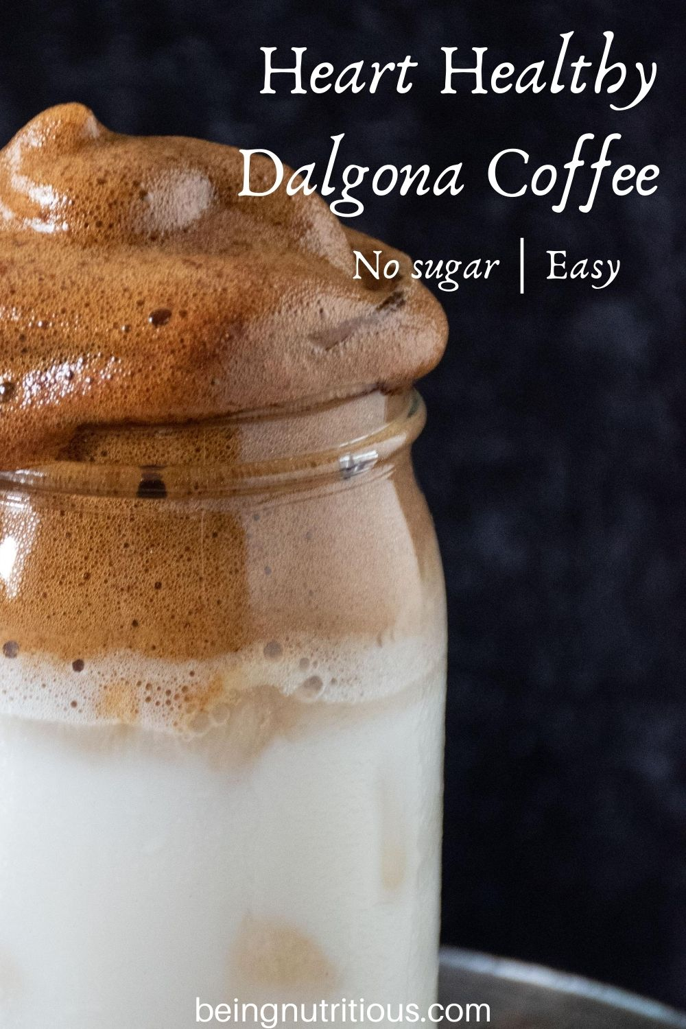 """Close up of whipped coffee over iced almond milk in a Mason jar with text overlay: """"Heart Healthy Dalgona Coffee, no sugar; easy"""""""