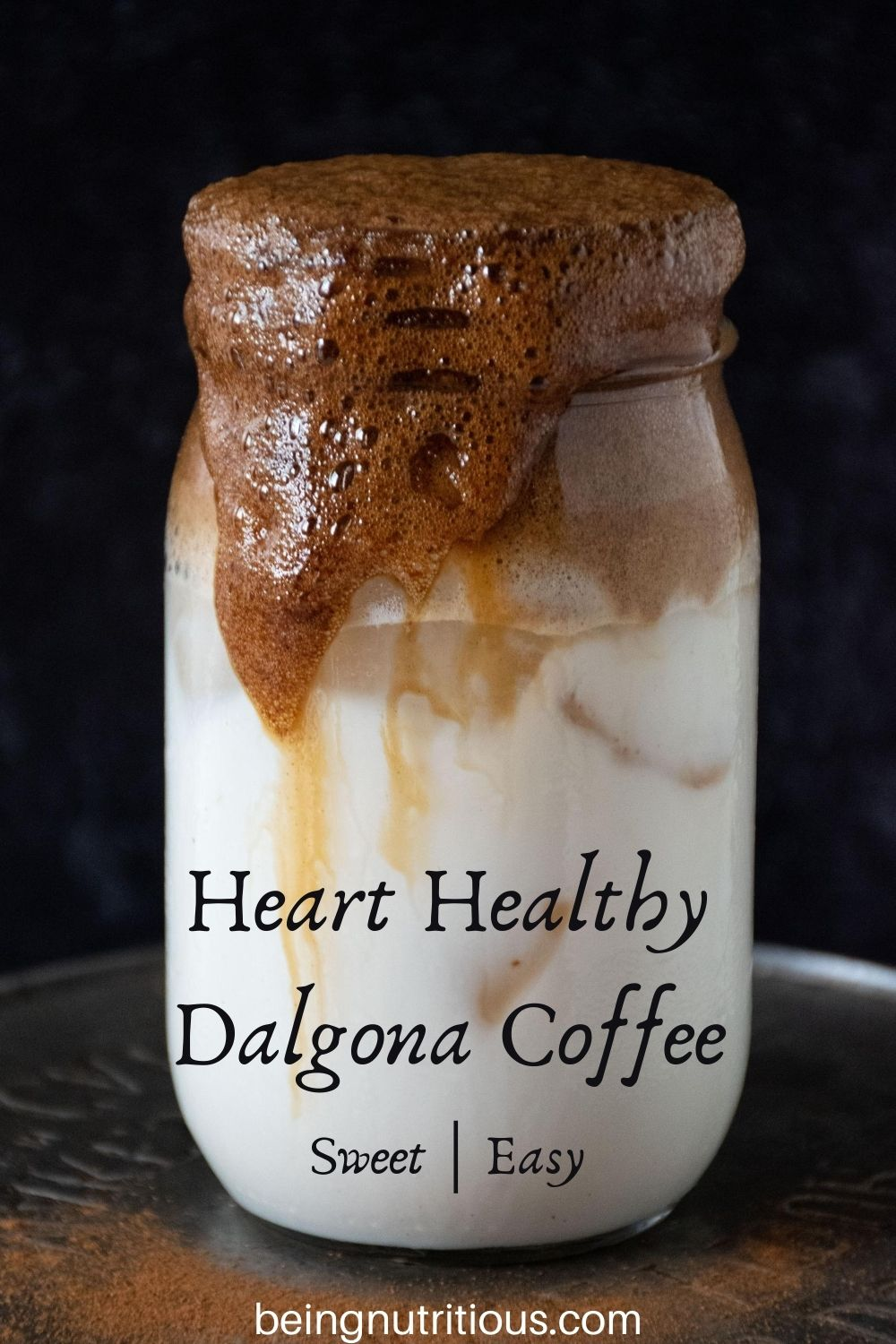 Whipped coffee over iced almond milk in a Mason jar with streams of coffee running down the side of the jar. Text overlay: &quote;Heart Healthy Dalgona Coffee, sweet; easy""