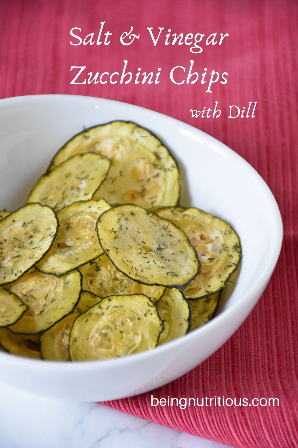 Zucchini chips in a white bowl with a red napkin under it.