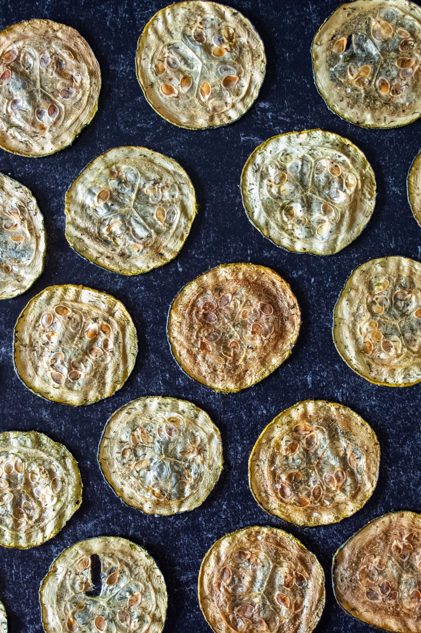 Overhead shot of zucchini chips arranged on a dark background, in a single layer, equidistant apart.