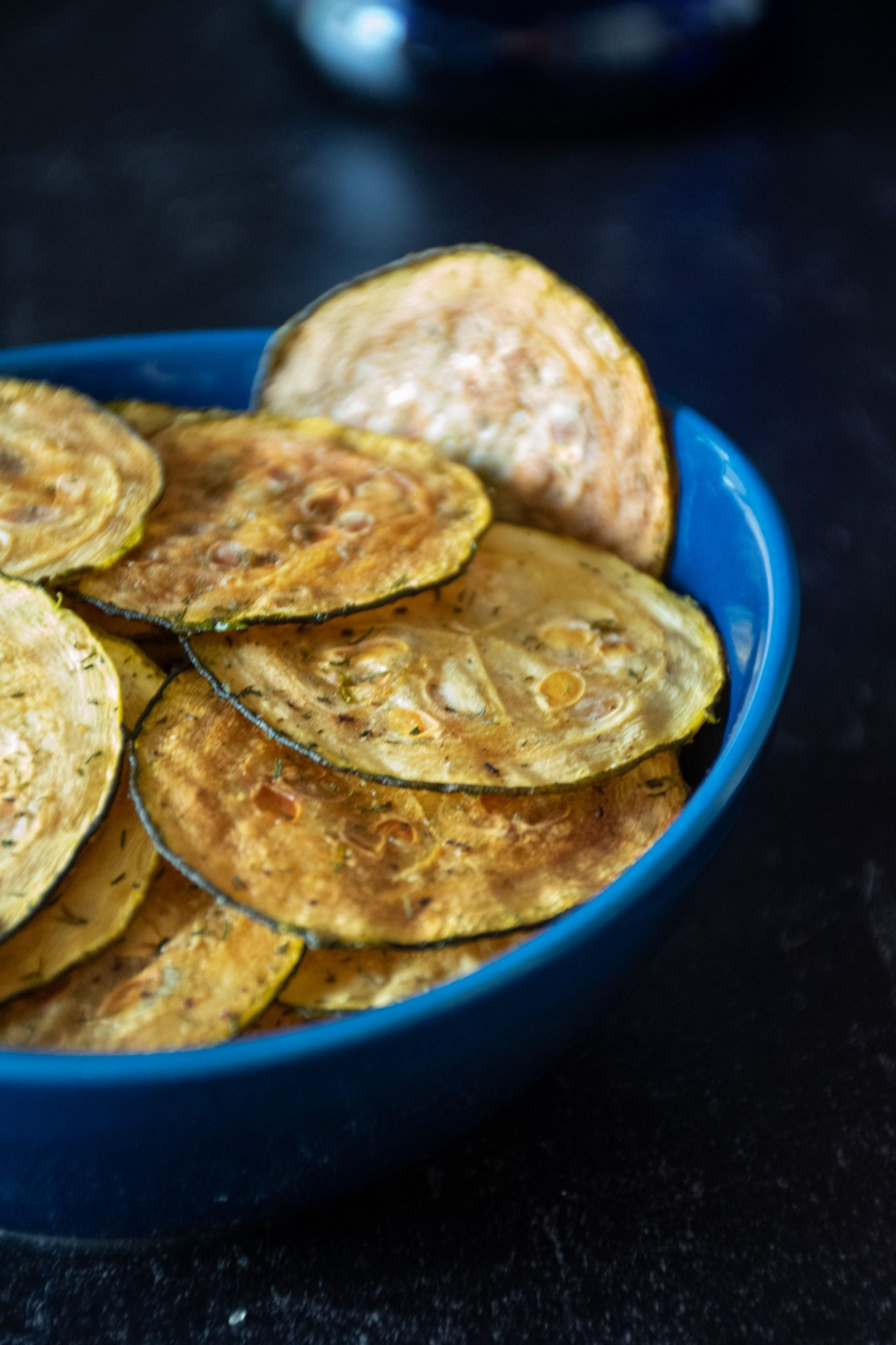 Zucchini chips in a blue bowl in front of dark background.