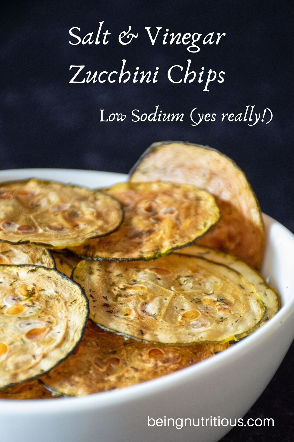 Zucchini chips in a white bowl in front of dark background.