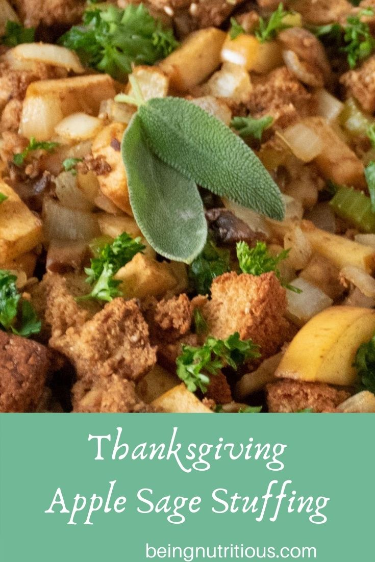 Close up of stuffing, garnished with 2 fresh sage leaves. Text overlay in a mint green rectangle: Thanksgiving apple sage stuffing.
