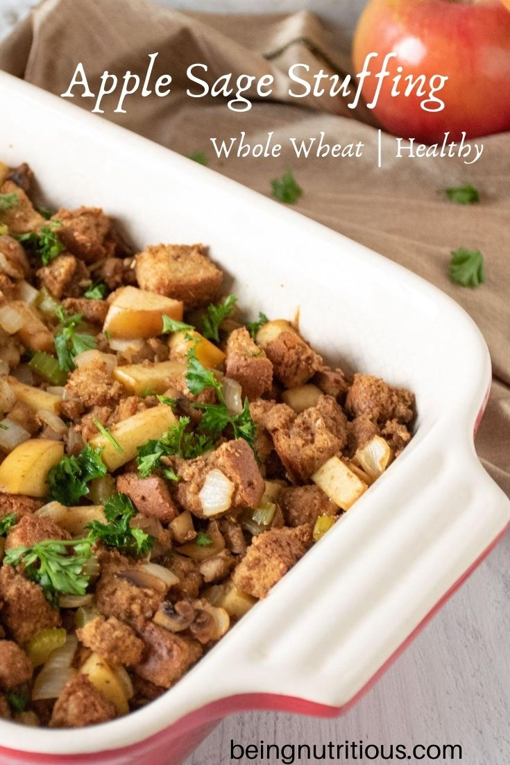 Stuffing in a large casserole dish. Whole apples visible in background. Text overlay: Apple sage stuffing, whole wheat, healthy.