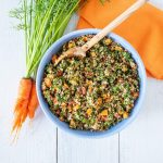 Overhead shot of carrot top tabbouleh in a blue bowl, half of the bowl shown, with a bunch of carrots with the tops still attached lying beside the bowl.