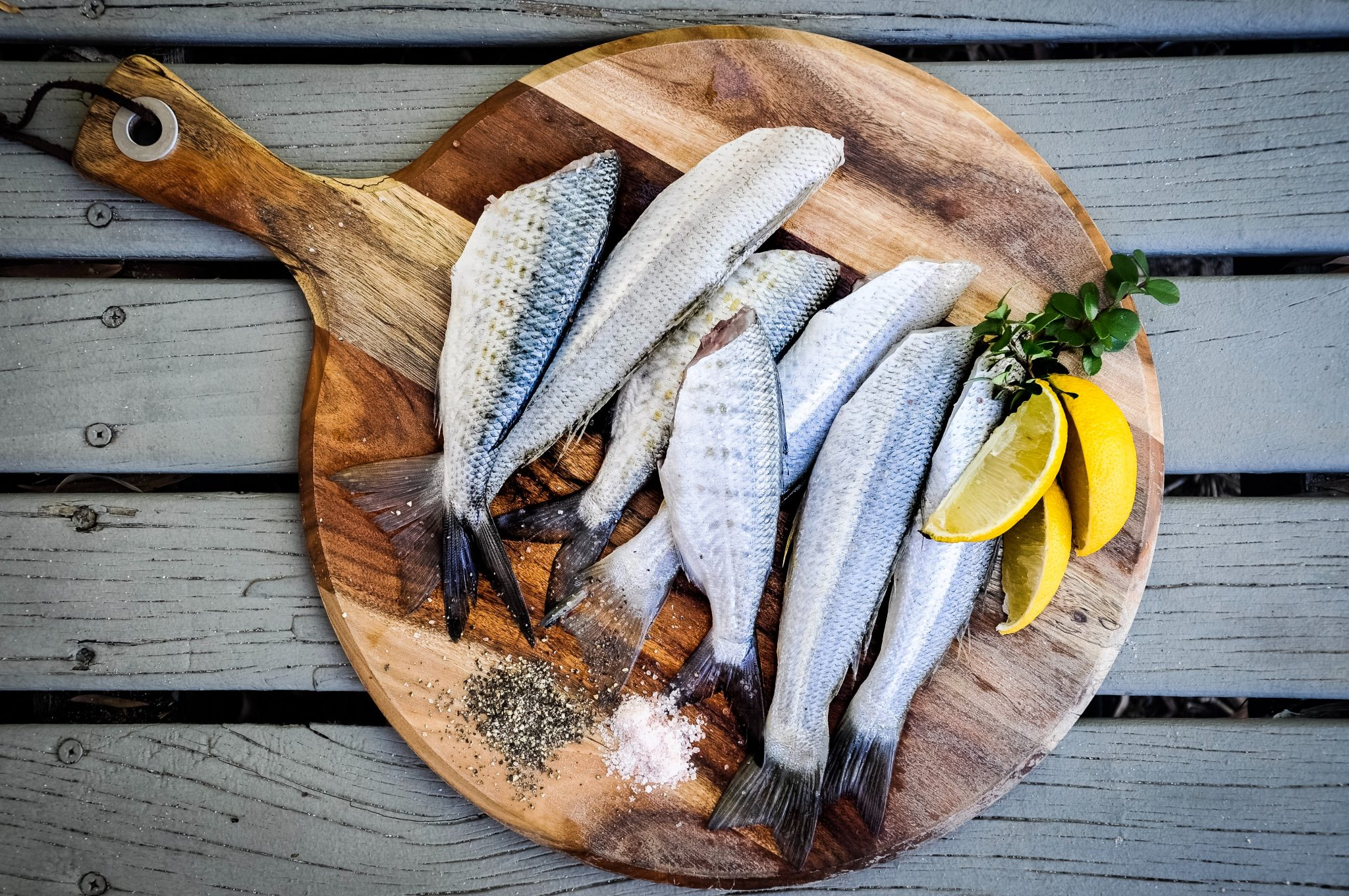 Seven butchered fish on a round cutting board, with lemon slices and salt and pepper