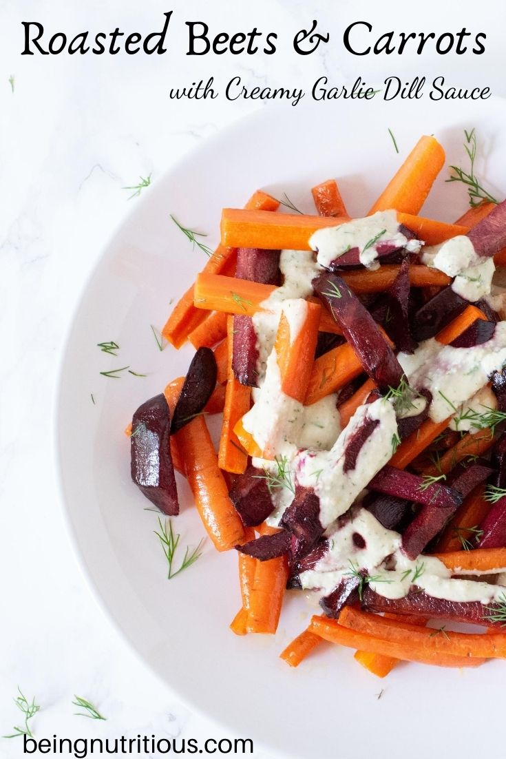 Roasted beets and carrots, cut into sticks, drizzled with garlic dill sauce on a white plate. Text overlay: Roasted Beets and Carrots with Creamy Garlic Dill Sauce.