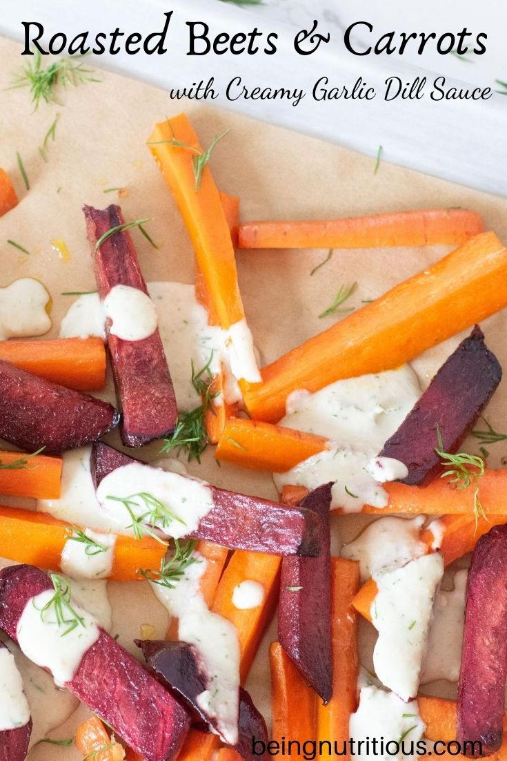Close up of beets and carrots, cut into thick sticks, roasted, drizzled with garlic dill sauce, on the baking sheet. Text overlay: Roasted Beets and Carrots with creamy garlic dill sauce.