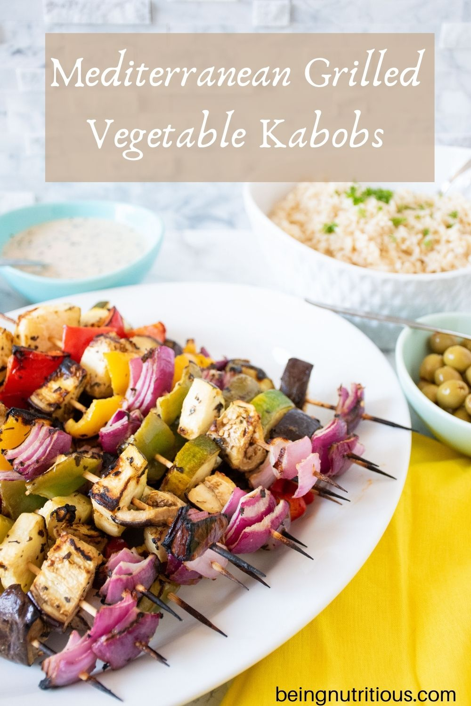 Serving platter with vegetable skewers piled on. Text overlay: Mediterranean Grilled Vegetable Kabobs.