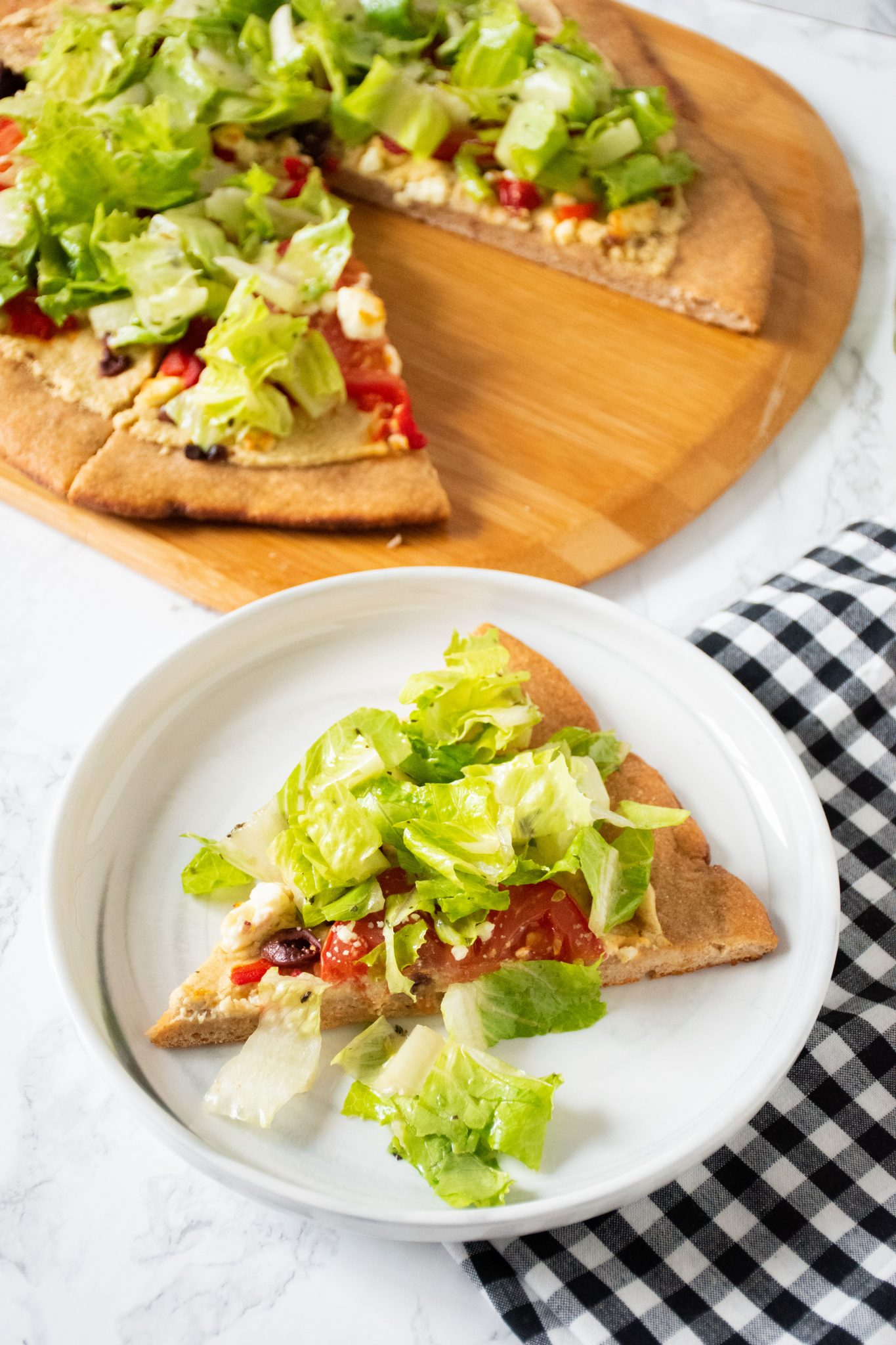 Slice of pizza on a plate. In background is the rest of the pizza on a peel, with whole wheat crust, topped with salad.