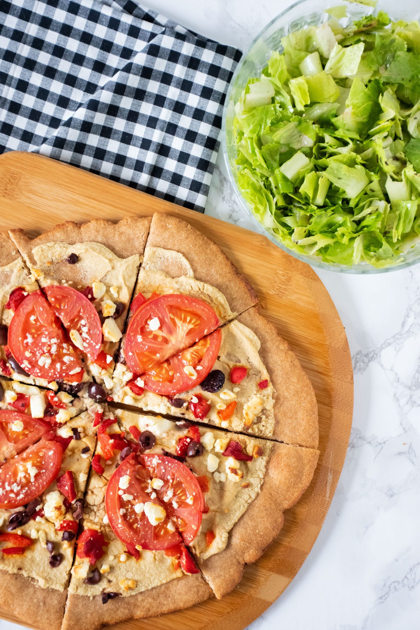 Whole grain pizza on a peel, with bowl of salad in background.