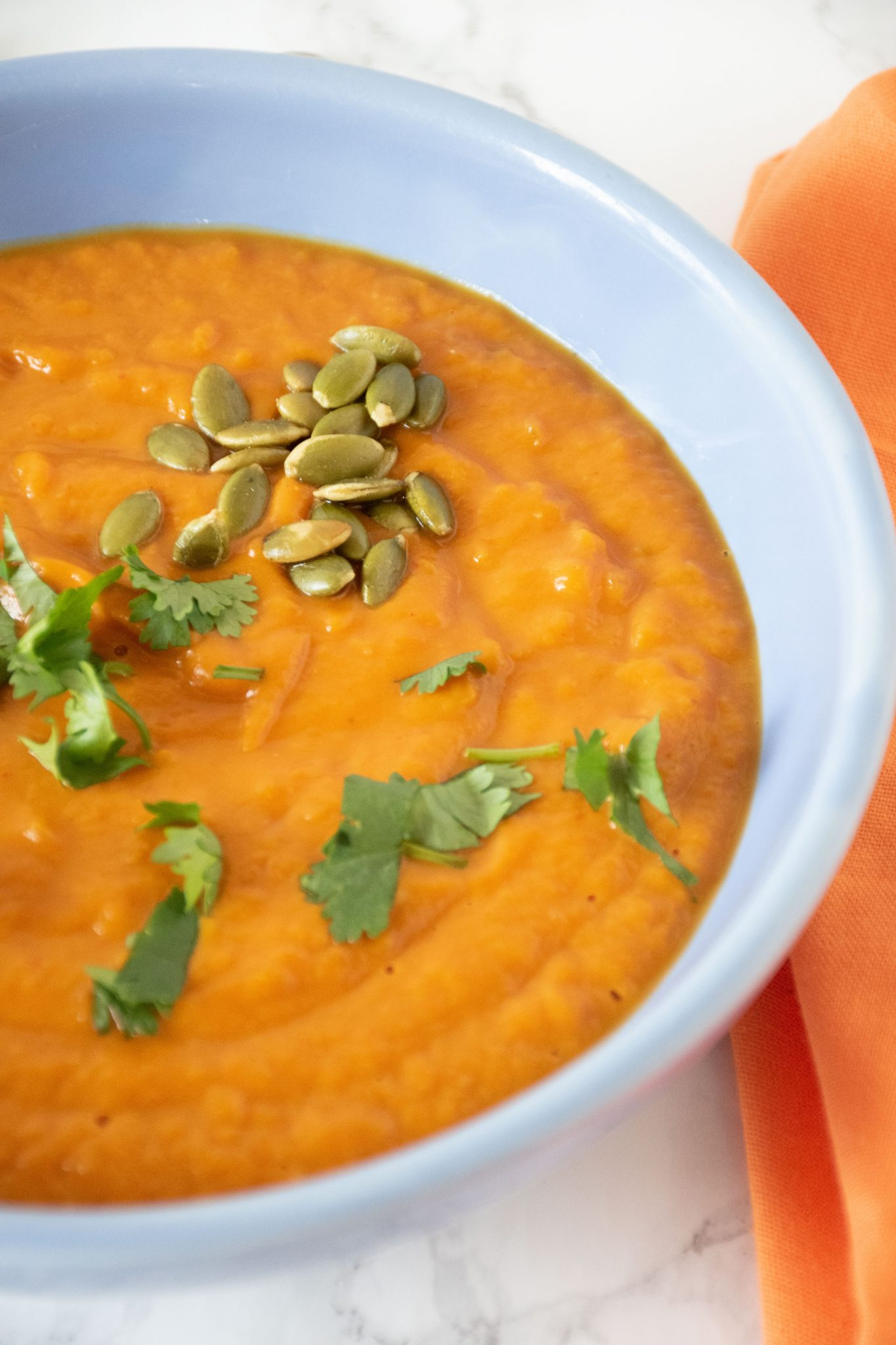 Pumpkin soup in a blue bowl, garnished with cilantro and pepitas.