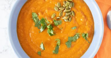 Overhead shot of pumpkin soup in a blue bowl, garnished with cilantro and pepitas.