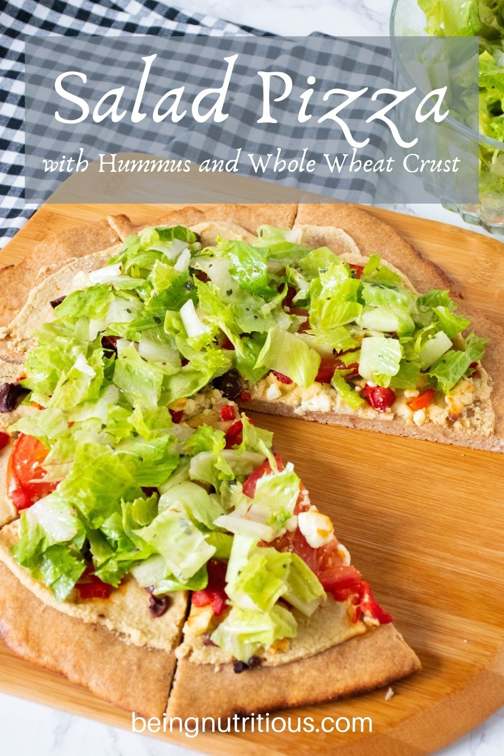 Pizza on a peel, with whole wheat crust, topped with salad. Text overlay: Salad Pizza with Hummus and Whole Wheat Crust.