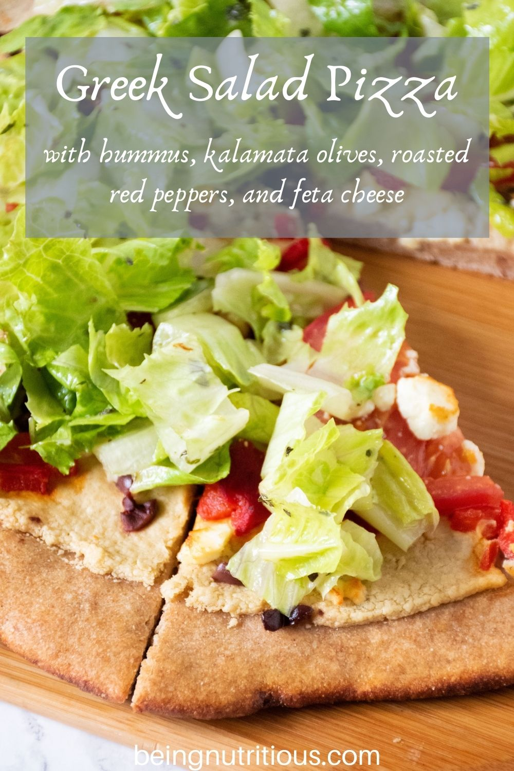 Pizza on a peel, with whole wheat crust, topped with salad. Text overlay: Greek Salad Pizza with hummus, kalamata olives, roasted red peppers, and feta cheese.