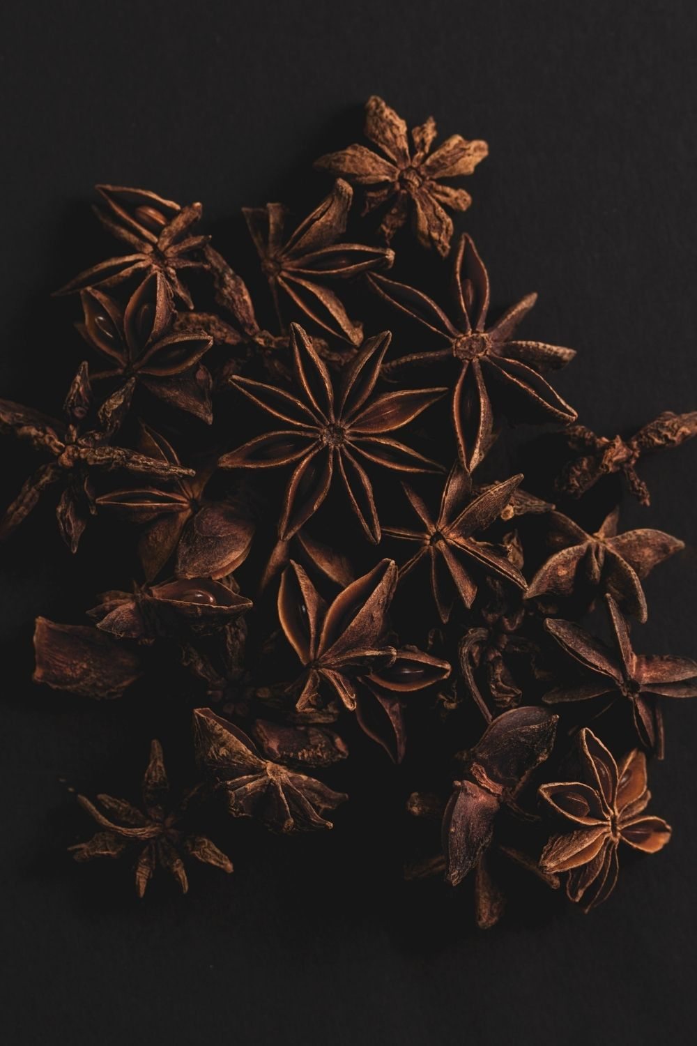 Many star anise pods on a dark background.