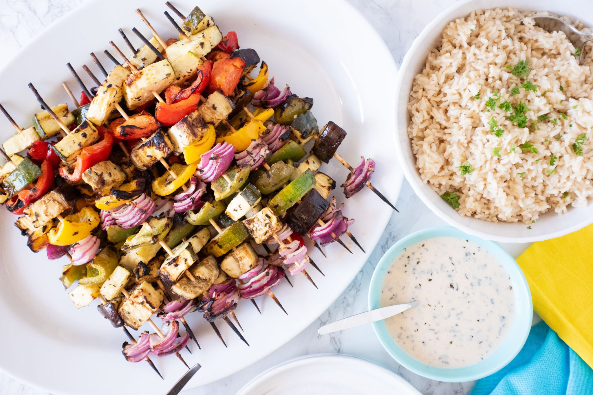 Serving platter with vegetable skewers piled on. A bowl of rice and marinade to the side.