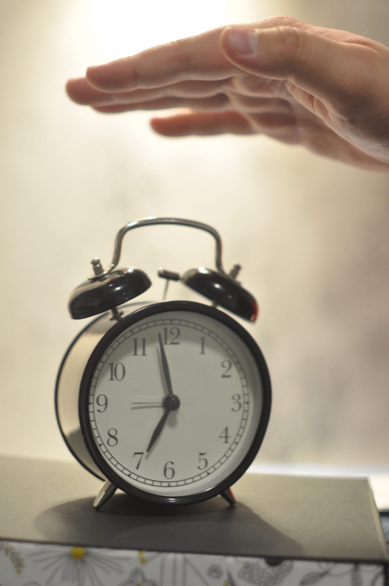 A hand turning off an alarm clock.