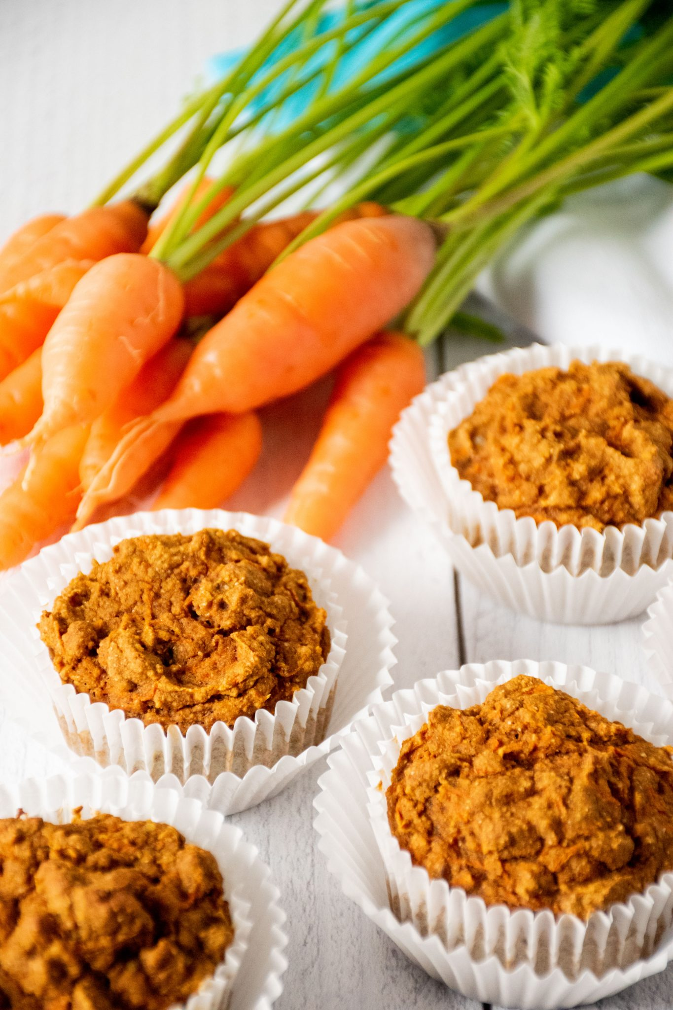 Muffins on a table with fresh carrots.