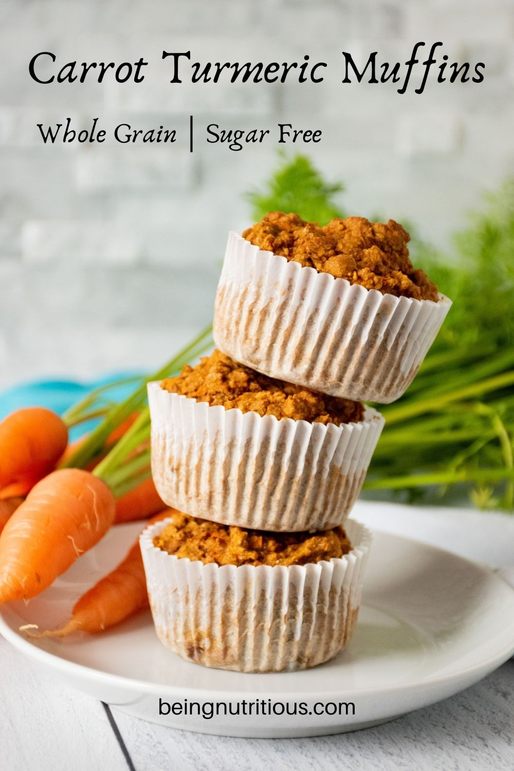 Stack of 3 muffins on a plate with fresh carrots in the background. Text overlay: Carrot Turmeric Muffins; whole grain, sugar free.