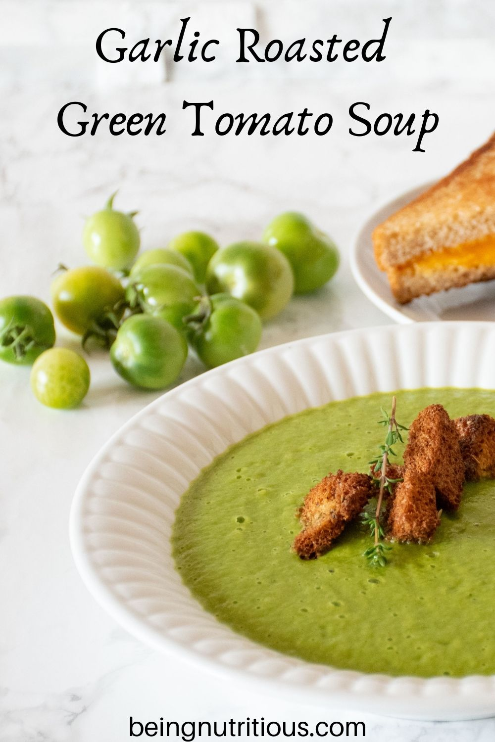 Green soup in a bowl with homemade croutons. Whole green grape tomatoes in background. Text overlay: Garlic Roasted Green Tomato Soup.